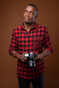 Foto de estúdio de um jovem africano contra um fundo marrom