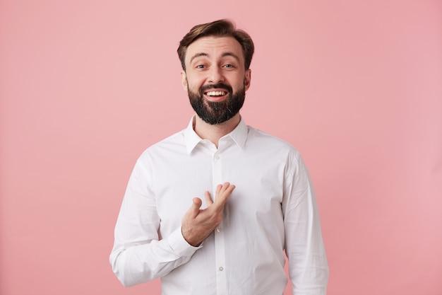 Foto de estúdio de um jovem barbudo homem de cabelos escuros olhando feliz para a frente com um sorriso largo, vestido com roupas formais enquanto posava sobre uma parede rosa, mostrando seus dentes brancos perfeitos