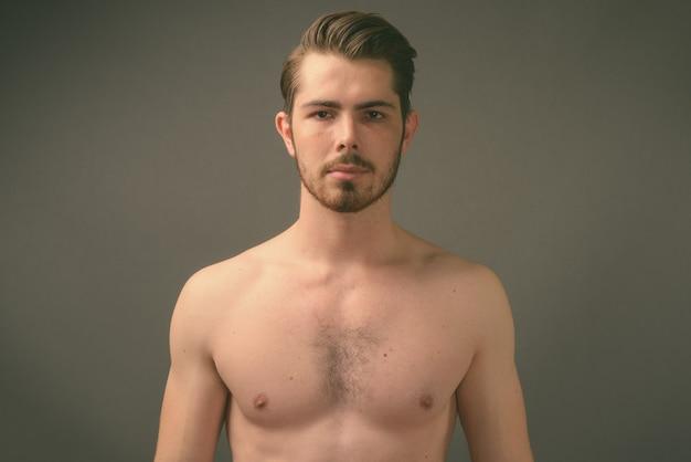 Foto de estúdio de um jovem bonito barbudo sem camisa contra uma parede cinza