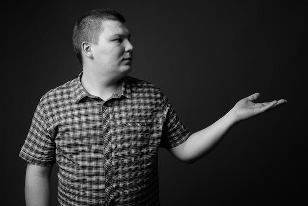 Foto de estúdio de um jovem com excesso de peso vestindo uma camisa quadriculada roxa contra uma parede cinza