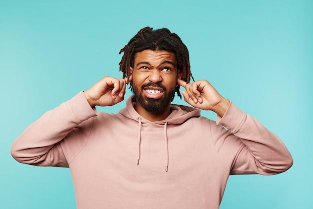 Foto de estúdio de um jovem de olhos castanhos e pele escura, colocando os dedos indicadores nas orelhas e franzindo a testa com descontentamento enquanto olha para cima, posando sobre um fundo azul