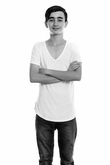 Foto de estúdio de um jovem e bonito adolescente persa isolado contra um fundo branco em preto e branco