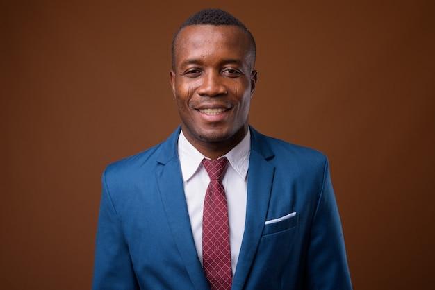 Foto de estúdio de um jovem empresário africano contra um fundo marrom
