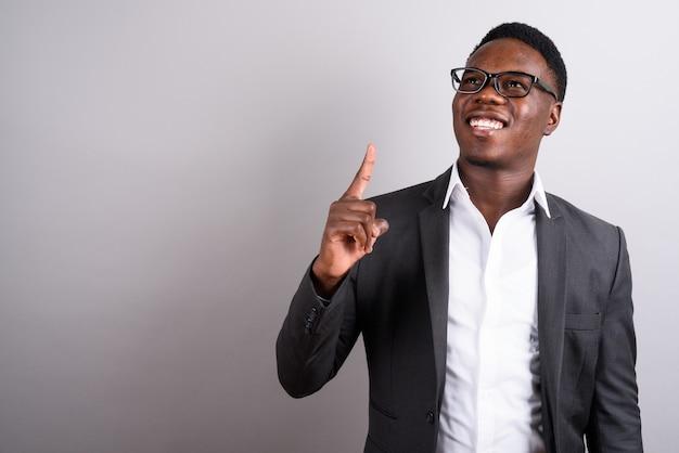 Foto de estúdio de um jovem empresário africano usando terno e óculos contra um fundo branco