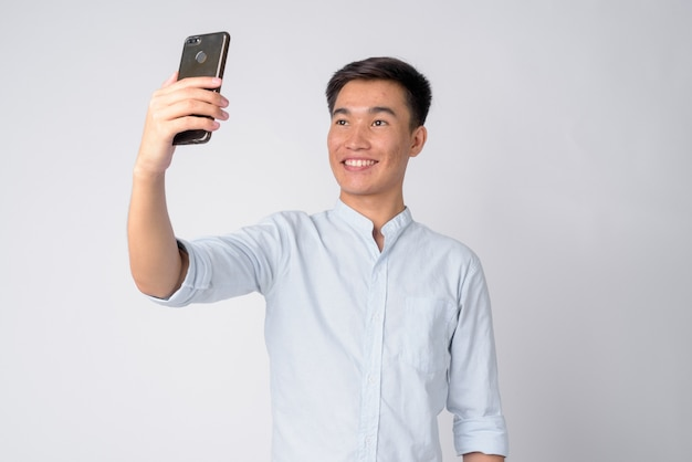 Foto de estúdio de um jovem empresário asiático bonito contra um fundo branco