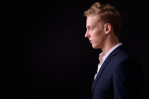 Foto de estúdio de um jovem empresário escandinavo bonito com cabelo loiro em um terno contra um fundo preto
