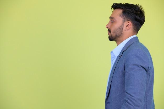 Foto de estúdio de um jovem empresário persa barbudo bonito em terno contra chroma key com fundo verde