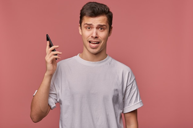 Foto de estúdio de um jovem homem de cabelos escuros com corte de cabelo curto, segurando o smartphone na mão, olhando para a câmera com rosto confuso, testa enrugada e carranca, posando sobre fundo rosa