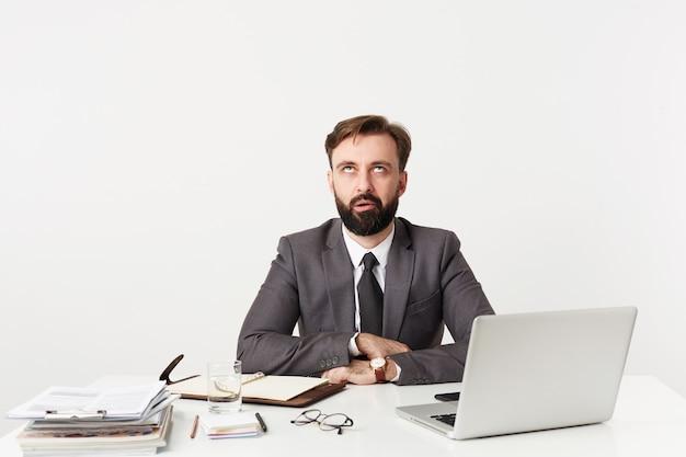 Foto de estúdio de um jovem homem moreno irritado com barba sentado à mesa de trabalho e mantendo as mãos postas na bancada, olhando para cima com beicinho enquanto posava sobre uma parede branca