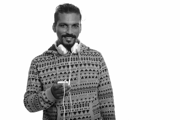 Foto de estúdio de um jovem indiano barbudo bonito usando um capuz contra o branco em preto e branco