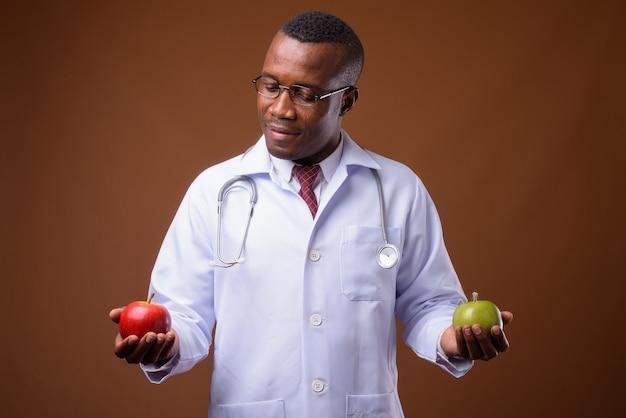 Foto de estúdio de um jovem médico africano contra um fundo marrom