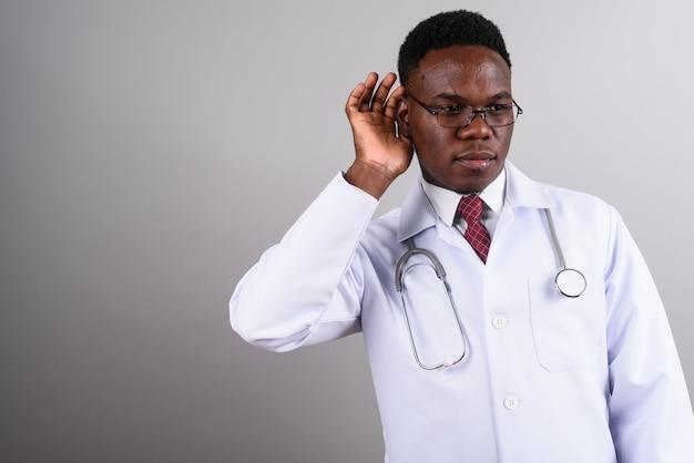 Foto de estúdio de um jovem médico africano usando óculos contra um fundo branco