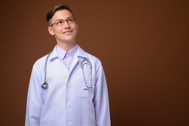 Foto de estúdio de um jovem médico bonito contra um fundo marrom