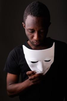 Foto de estúdio de um jovem negro africano em um quarto escuro segurando uma máscara