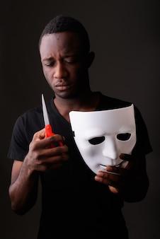 Foto de estúdio de um jovem negro africano segurando uma máscara e uma tesoura