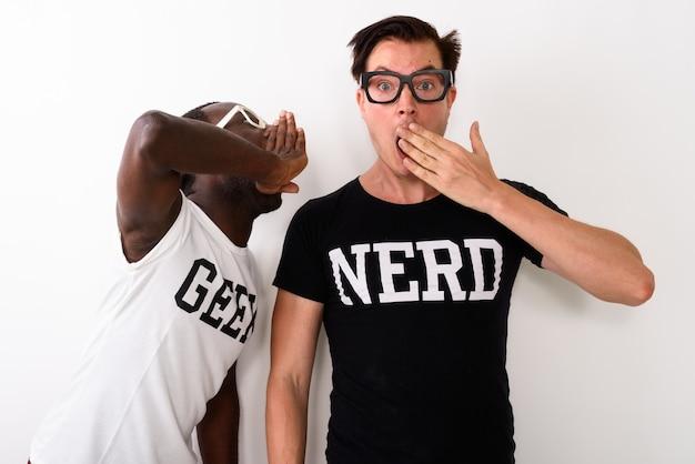 Foto de estúdio de um jovem negro geek sussurrando enquanto eur