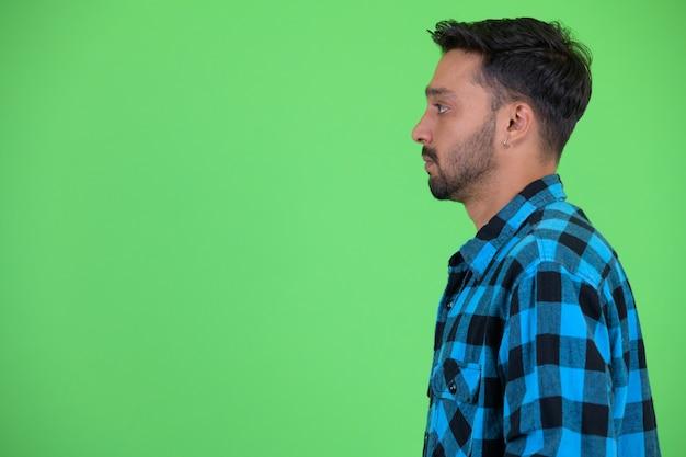 Foto de estúdio de um jovem persa barbudo e bonito homem hippie contra chroma key com fundo verde