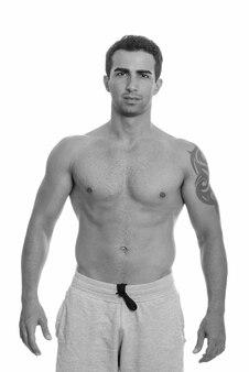 Foto de estúdio de um jovem persa musculoso e bonito sem camisa, isolado contra um fundo branco em preto e branco