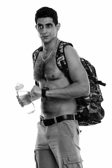 Foto de estúdio de um jovem persa musculoso segurando uma garrafa de água enquanto pensa e verifica o tempo sem camisa