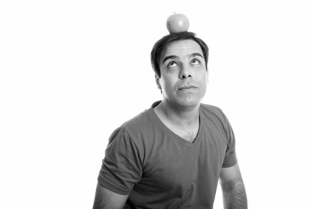 Foto de estúdio de um jovem persa pensando enquanto olha para uma maçã isolada no topo da cabeça