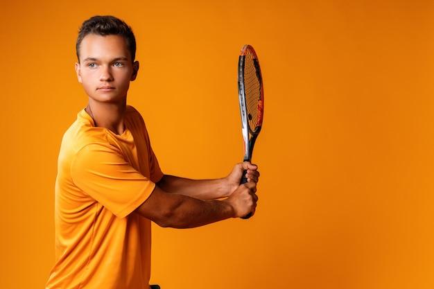 Foto de estúdio de um jovem tenista segurando uma raquete contra um fundo laranja close-up