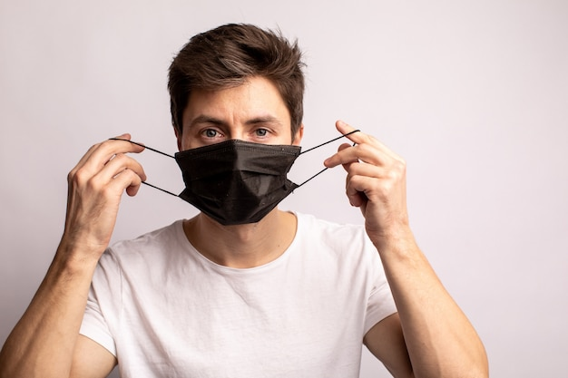 Foto de estúdio de um jovem vestindo uma máscara preta, olhando para a câmera, isolada no branco