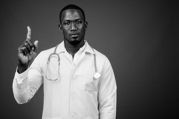 Foto de estúdio de um médico africano bonito usando óculos contra uma parede cinza