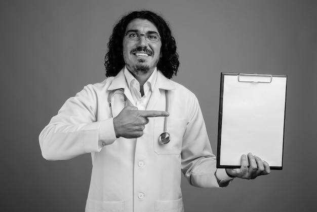 Foto de estúdio de um médico bonito com bigode contra um fundo cinza em preto e branco