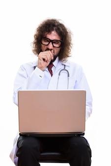 Foto de estúdio de um médico cansado usando um laptop enquanto boceja
