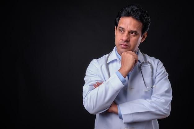 Foto de estúdio de um médico indiano maduro contra um fundo preto