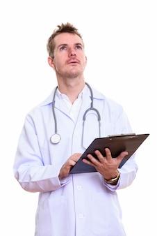 Foto de estúdio de um médico segurando uma prancheta enquanto pensa
