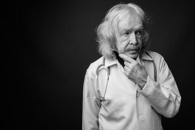 Foto de estúdio de um médico sênior com bigode contra uma parede cinza