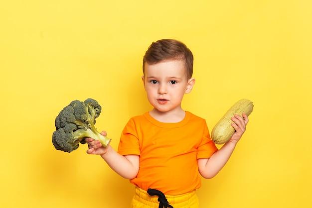Foto de estúdio de um menino segurando brócolis fresco e abobrinha fresca em uma parede amarela.