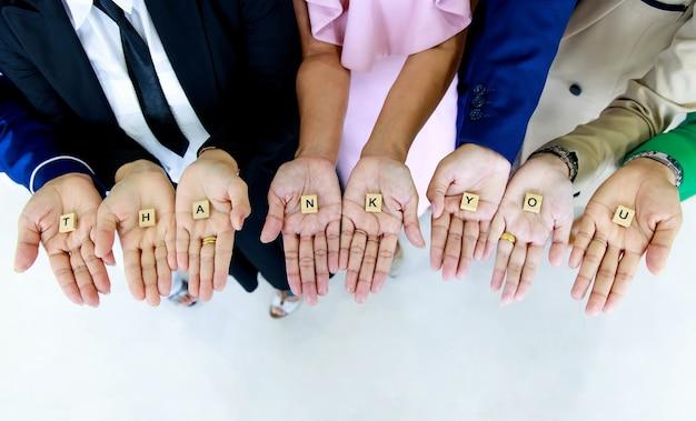 Foto de estúdio de um pequeno bloco de cubos de madeira, letras de agradecimento, alfabetos mantidos nas mãos por funcionários sem rosto não identificados e irreconhecíveis, em trajes de negócios, para mostrar apreço aos clientes ou colegas.