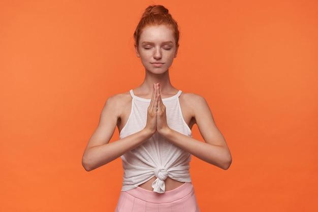 Foto de estúdio de uma adorável jovem ruiva com penteado coque usando blusa branca e saia rosa, levantando as mãos com as palmas das mãos dobradas em gesto de namastê, meditando com os olhos fechados sobre fundo laranja