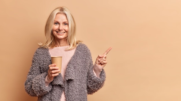 Foto de estúdio de uma adorável loira de cinquenta anos sorrindo positivamente segurando um copo descartável de bebida quente e usando um casaco de pele indica isolado sobre uma parede marrom