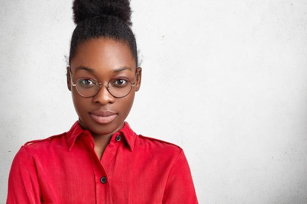 Foto de estúdio de uma bela aluna com pele escura, saudável e pura, aparência atraente, usando óculos redondos e roupas vermelhas, posa contra uma parede de concreto branca com espaço de cópia para seu anúncio