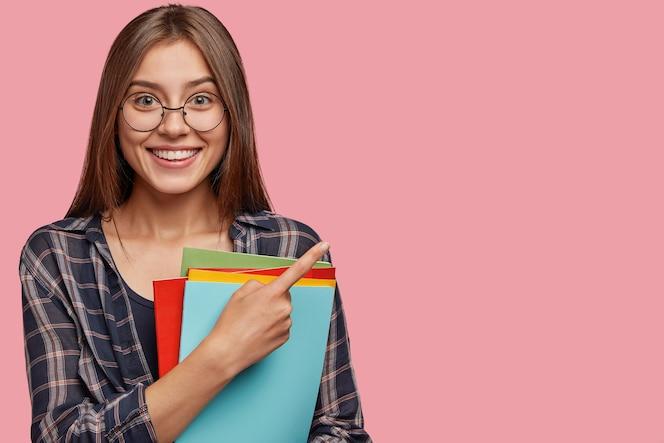 foto de estúdio de uma bela jovem empresária posando contra a parede rosa com óculos