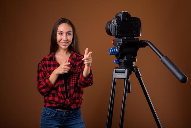 Foto de estúdio de uma bela jovem fazendo um vlog contra um fundo marrom