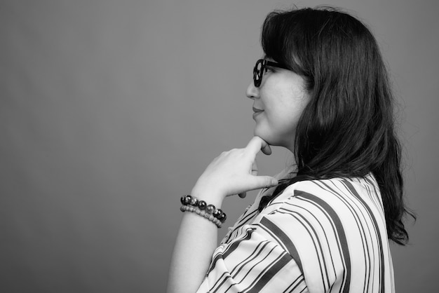 Foto de estúdio de uma bela mulher japonesa madura contra o cinza em preto e branco