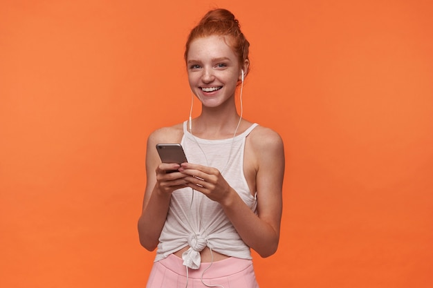 Foto de estúdio de uma encantadora jovem cabeça de leitura com penteado coque posando sobre fundo laranja, segurando o smartphone nas mãos levantadas e ouvindo música com fones de ouvido