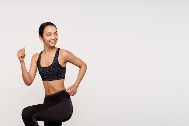 Foto de estúdio de uma feliz jovem esguia de cabelos castanhos com penteado casual de bom humor enquanto faz exercícios matinais, em pé sobre uma parede branca