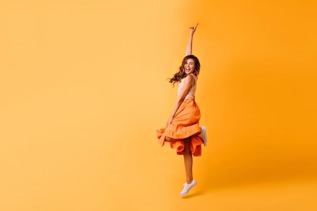 Foto de estúdio de uma garota bonita com saia laranja e sapatos brancos. mulher ruiva animada pulando no amarelo.