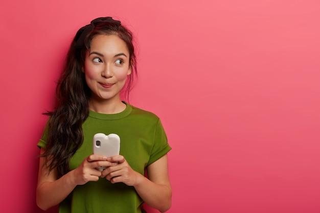 Foto de estúdio de uma garota coreana pensativa e positiva usando telefone celular para bater papo online, desvia o olhar e usa roupas casuais
