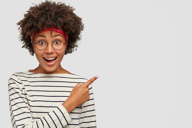 Foto de estúdio de uma garota de pele escura usando óculos redondos transparentes