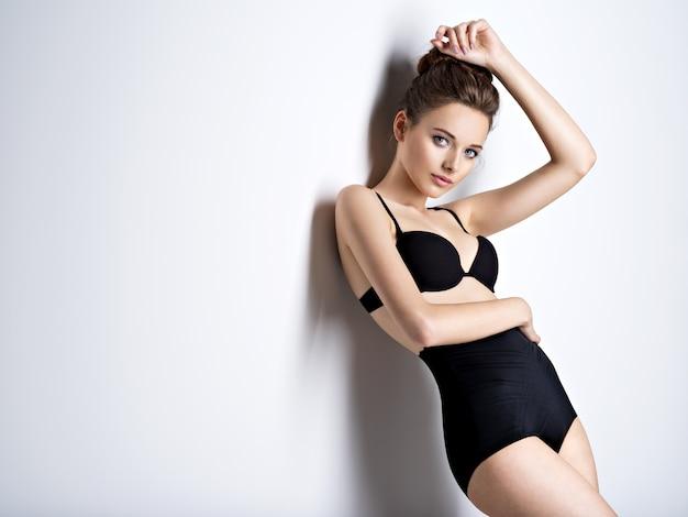 Foto de estúdio de uma garota linda e sexy com cabelo castanho usando lingerie preta