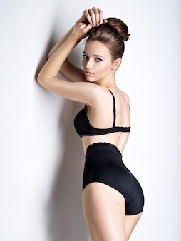 Foto de estúdio de uma garota linda e sexy com cabelo comprido, vestindo lingerie preta