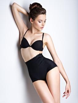 Foto de estúdio de uma garota linda e sexy com corpo perfeito usando lingerie preta