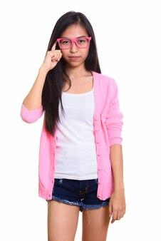 Foto de estúdio de uma jovem adolescente asiática com o dedo na cabeça