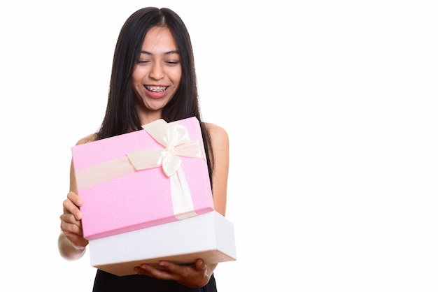 Foto de estúdio de uma jovem adolescente asiática feliz sorrindo ao abrir um presente